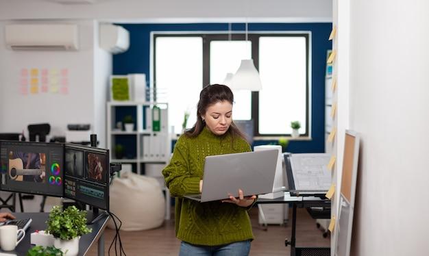 Mitarbeiter, der einen laptop im büro einer kreativagentur hält und ein kundenvideoprojekt in der postproduktionssoftware bearbeitet