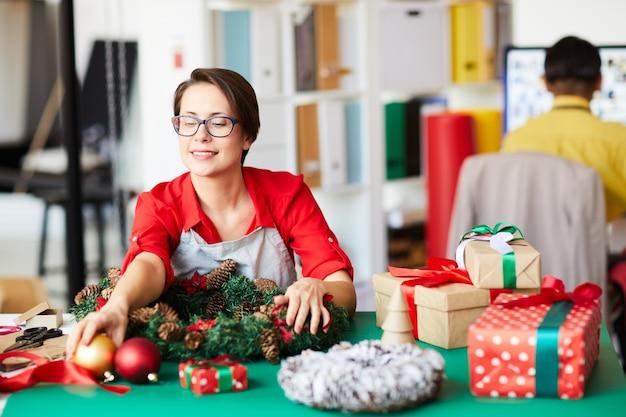Mitarbeiter, der einen weihnachtskranz macht und geschenkboxen einwickelt