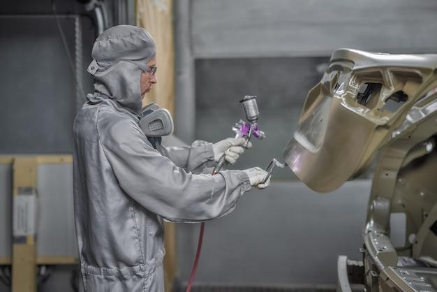 Mitarbeiter der lackiererei bereitet die karosserie für die lackierung vor.