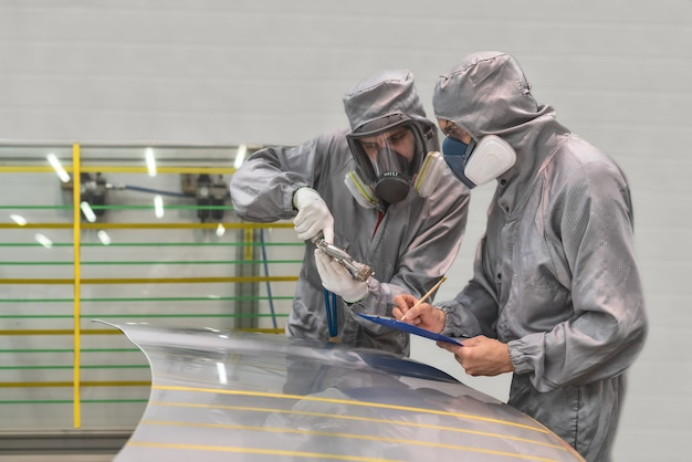 Mitarbeiter der lackiererei der automobilfabrik führt schulungen zum lackieren von körperteilen durch