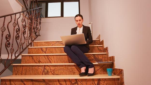 Mitarbeiter, der laptop verwendet, um den termin zu überarbeiten, der auf der treppe in der finanzgesellschaft sitzt. executive manager, der überstunden bei der arbeit auf treppenhausgeschäftsleuten macht, die in modernen finanzgebäuden arbeiten.