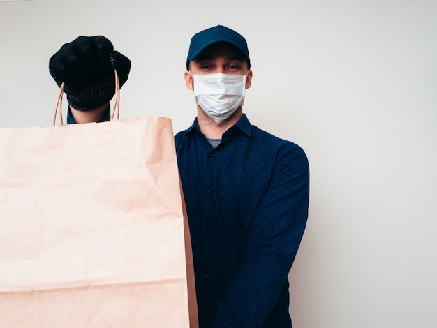 Mitarbeiter des lieferservices für lebensmittel, der bei der covid-19-pandemie ein blaues hemd, ein lager, eine maske und handschuhe trägt.