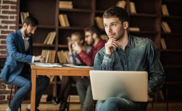 Mitarbeiter des unternehmens sitzt auf einem stuhl mit laptop