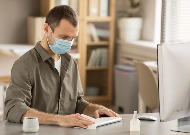 Mitarbeiter desinfiziert elektronisches gerät
