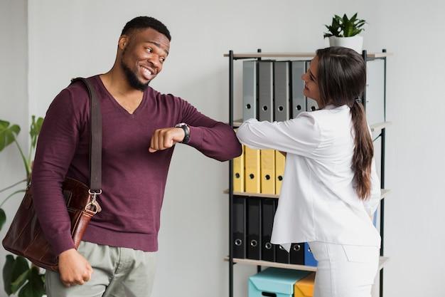 Mitarbeiter, die bei der arbeit während der pandemie die ellbogen berühren, um abstand zu halten
