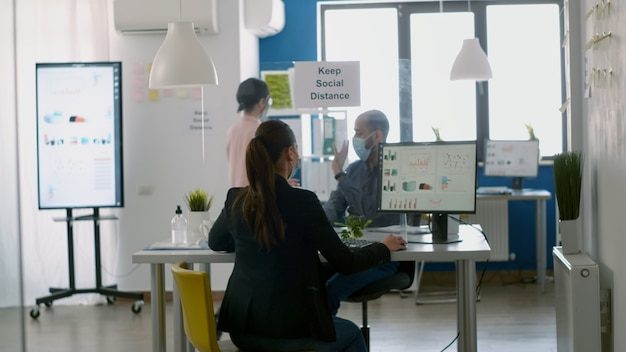 Mitarbeiter, die gesichtsmasken tragen, begrüßen sich mit dem ellbogen, während sie während der sperrung des coronavirus in einem neuen normalen firmenbüro arbeiten. das team respektiert die soziale distanzierung, um eine infektion mit dem virus zu verhindern