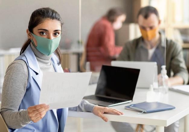 Mitarbeiter, die im büro eine gesichtsmaske tragen
