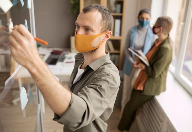 Mitarbeiter, die im büro gesichtsmasken tragen