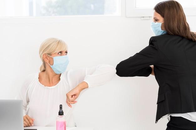 Mitarbeiter, die masken und ellbogen tragen, stoßen sich gegenseitig an
