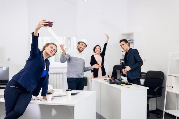 Mitarbeiter, die spaß im büro haben, posieren und selfies mit einem smartphone machen