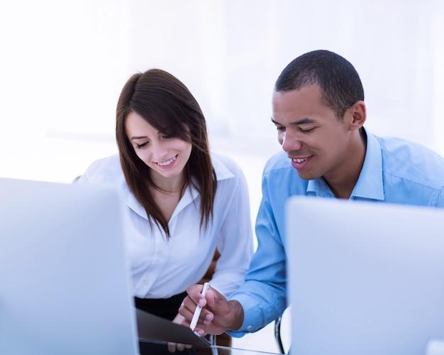 Mitarbeiter diskutieren finanzdokumente an einem schreibtisch