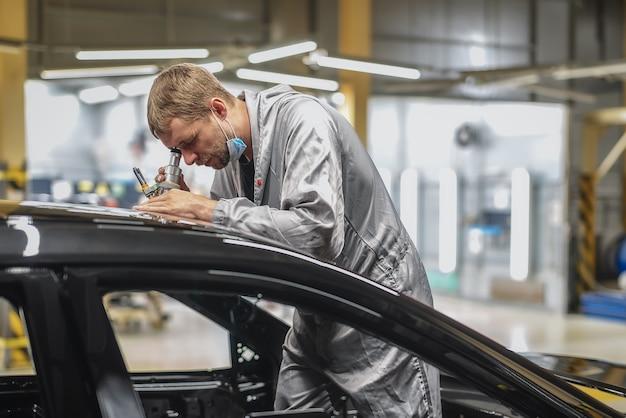 Mitarbeiter einer autofabrik überprüft die lackierqualität mit einem mikroskop
