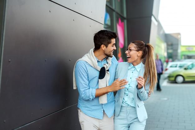 Mitarbeiter gehen von der arbeit und lachen, während sie auf der straße gehen. frau, die papierkram hält, während mann tablette hält.