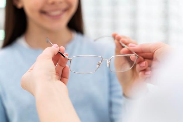 Mitarbeiter helfen mädchen, brille anzuprobieren