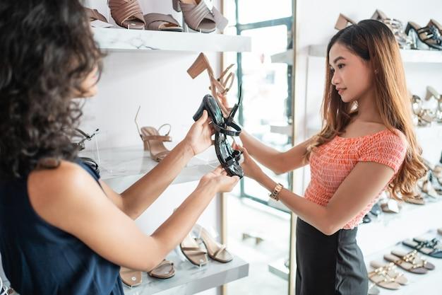 Mitarbeiter hilft kunden beim kauf neuer schuhe