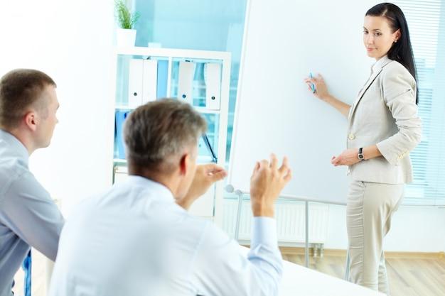 Mitarbeiter ihre strategie auf dem whiteboard zu erklären