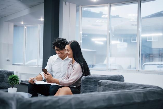 Mitarbeiter im büro, die etwas lustiges material auf dem smartphone lächeln und aufpassen