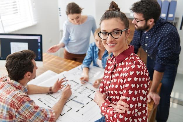 Mitarbeiter im büro mit architekturplänen und einem computer. manager-konzept