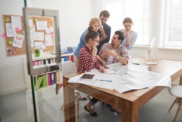 Mitarbeiter im büro mit architekturplänen und einem computer