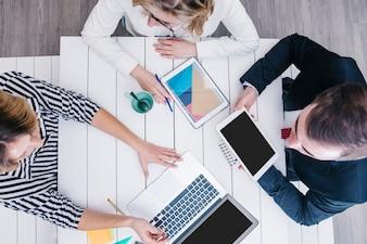 Mitarbeiter im Chat und mit Gadgets am Tisch