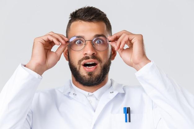 Mitarbeiter im gesundheitswesen, coronavirus, covid-19-pandemie und versicherungskonzept. nahaufnahme eines aufgeregten und beeindruckten hispanischen arztes im weißen kittel, aufgesetzter brille keuchend und erstaunt starrend.