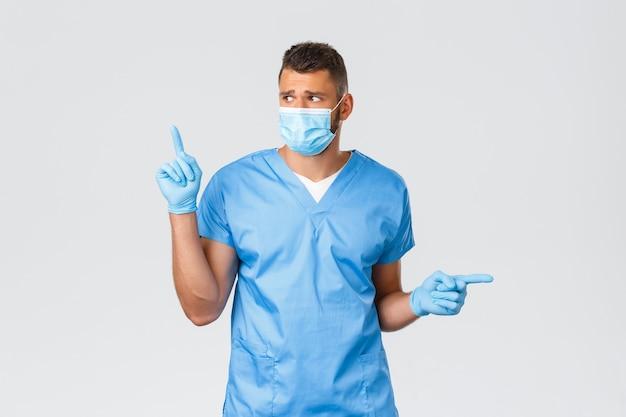 Mitarbeiter im gesundheitswesen, covid-19, coronavirus und präventionsviruskonzept. besorgter und verzweifelter, gutaussehender arzt, krankenschwester oder praktikant in peelings und medizinischer maske, schauen sie nach links und zeigen sie zur seite