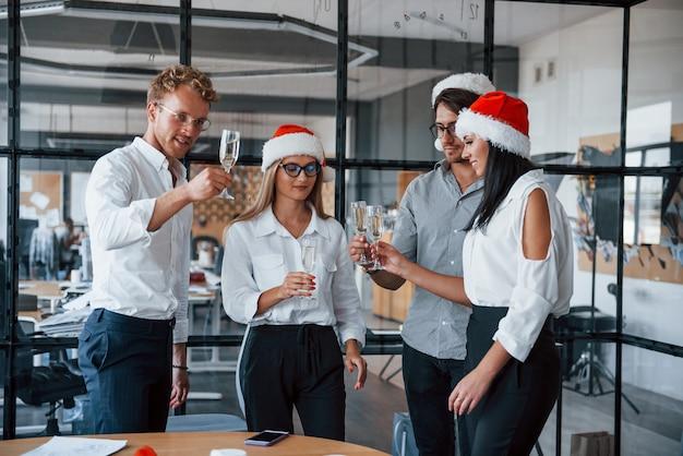 Mitarbeiter in formeller kleidung, gläsern mit champagner und in weihnachtsmützen feiern das neue jahr im büro.