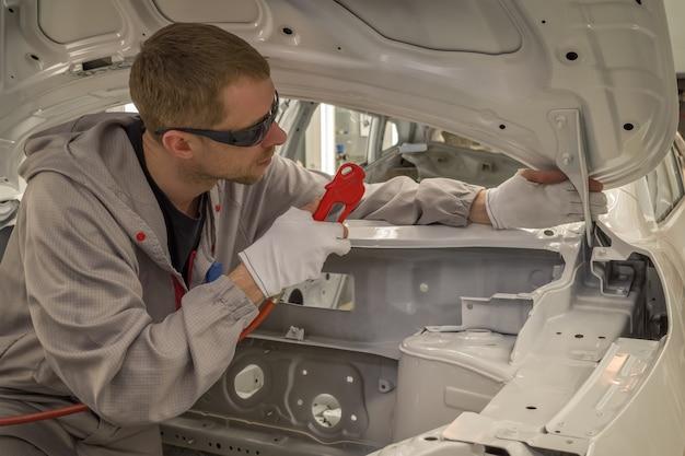 Mitarbeiter karosserielackiererei bereitet die oberfläche für die lackierung vor, entfernt staub