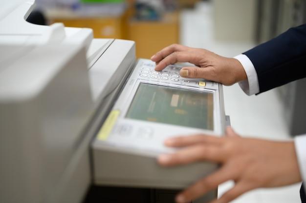 Mitarbeiter kopieren dokumente mit einem kopierer im büro.