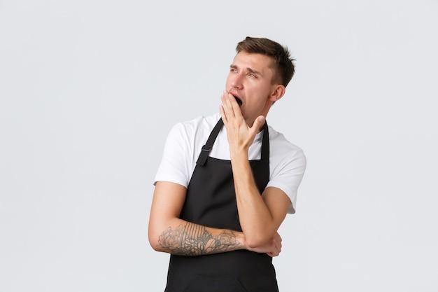 Mitarbeiter lebensmittelgeschäfte und café-konzept gelangweilt oder müde hübscher café-kellner in schwarzer schürze ...