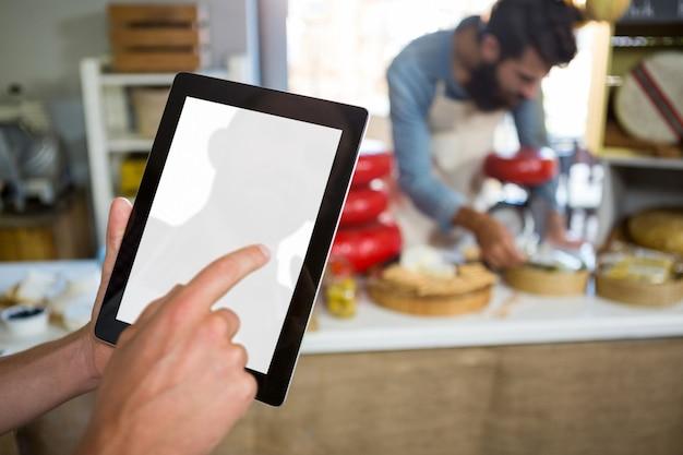 Mitarbeiter mit digitaler tablette am bäckertisch