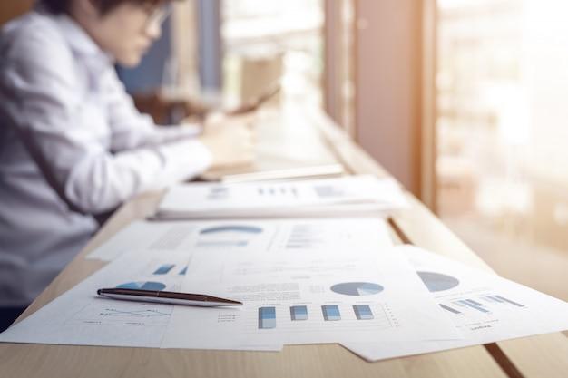 Mitarbeiter mit smartphone auf dem schreibtisch im büro
