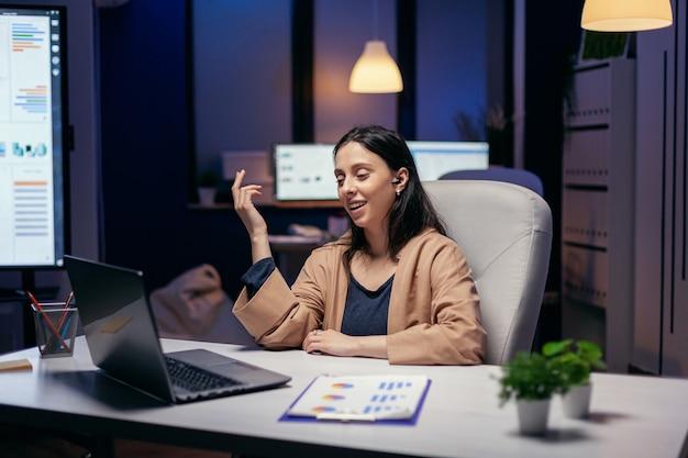Mitarbeiter mit videokonferenz, die überstunden am geschäftsarbeitsplatz machen. frau, die während einer videokonferenz mit kollegen nachts im büro an finanzen arbeitet.