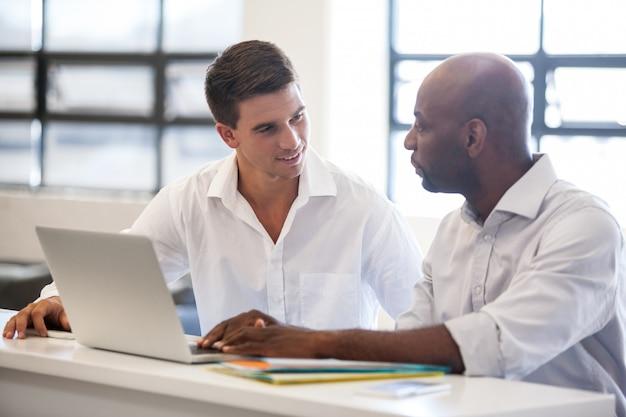 Mitarbeiter sprechen vor laptop