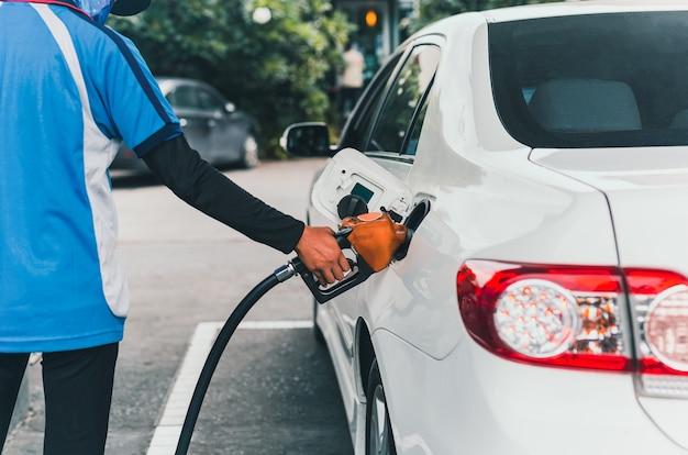 Mitarbeiter steckt zapfpistole in den tank und betankt auto mit benzin