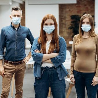 Mitarbeiter tragen gesichtsmasken bei der arbeit