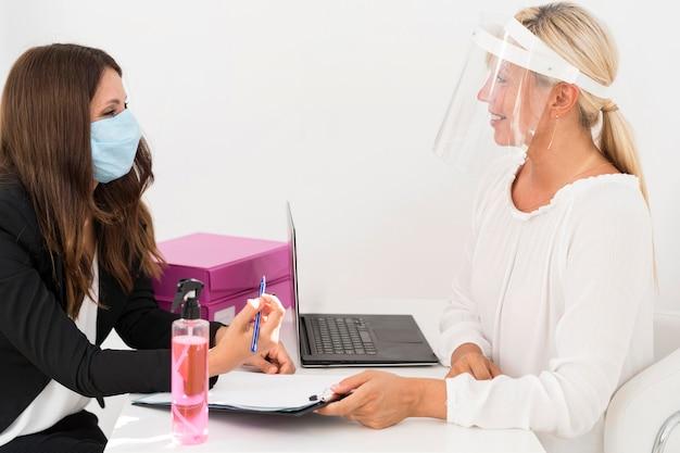Mitarbeiter tragen medizinische maske und gesichtsschutz