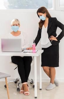 Mitarbeiter tragen schutzmaske und arbeiten