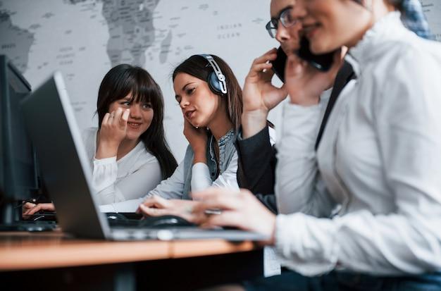 Mitarbeiter unterhalten sich. junge leute, die im call center arbeiten. neue angebote kommen