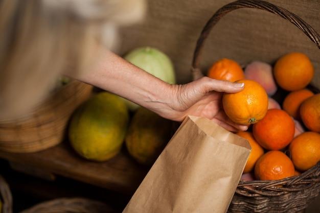 Mitarbeiter verpacken orangen in papiertüte