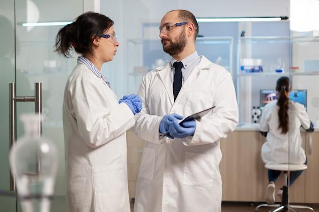Mitarbeiter von wissenschaftlern, die ein digitales tablet verwenden, das im medizinischen labor arbeitet