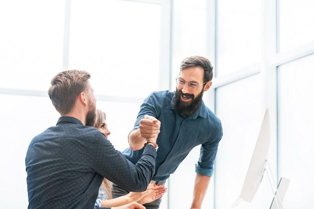 Mitarbeiter zeigen gemeinsam ihren erfolg. das konzept der teamarbeit