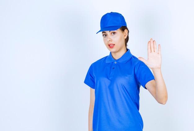 Mitarbeiterin der lieferfrau in blauer uniform, die ein stoppschild zeigt.