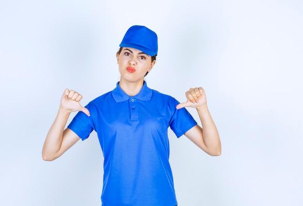Mitarbeiterin der lieferungsfrau in blauer uniform, die auf sich selbst steht und zeigt.