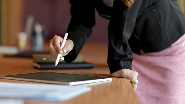 Mitarbeiterin des unternehmens lehnt sich an den schreibtisch und unterschreibt einen geschäftsvertrag auf einem digitalen tablet