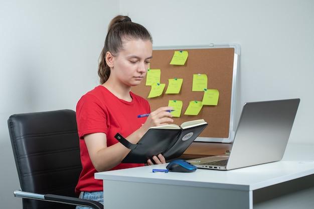 Mitarbeiterin, die am laptop arbeitet und sich notizen macht