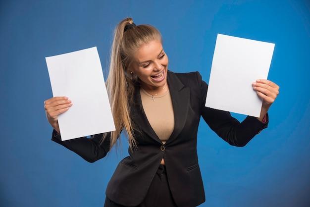 Mitarbeiterin, die dokumente kontrolliert und lacht.