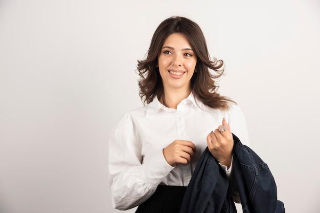 Mitarbeiterin, die ihre jacke weiß hält.