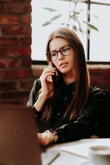 Mitarbeiterin, die im büro arbeitet und mit dem telefon spricht