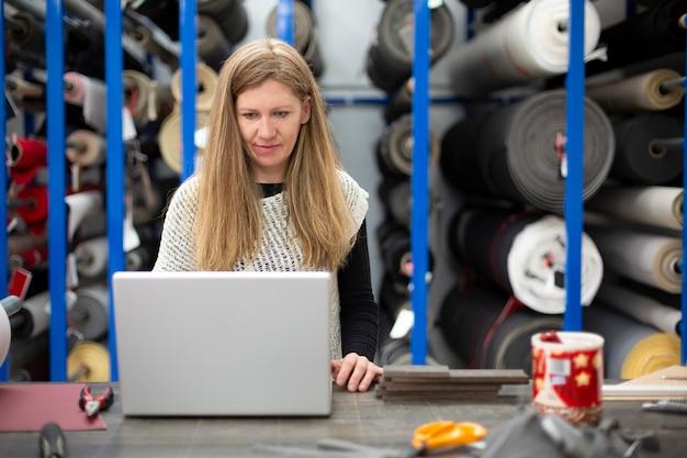 Mitarbeiterin eines textillagers an ihrem arbeitsplatz mit laptop Premium Fotos